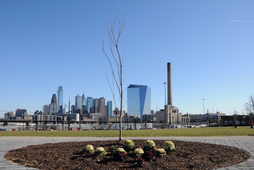 In the foreground is a courtyard in Drexel Park. In the distance is the Philadelphia skyline.