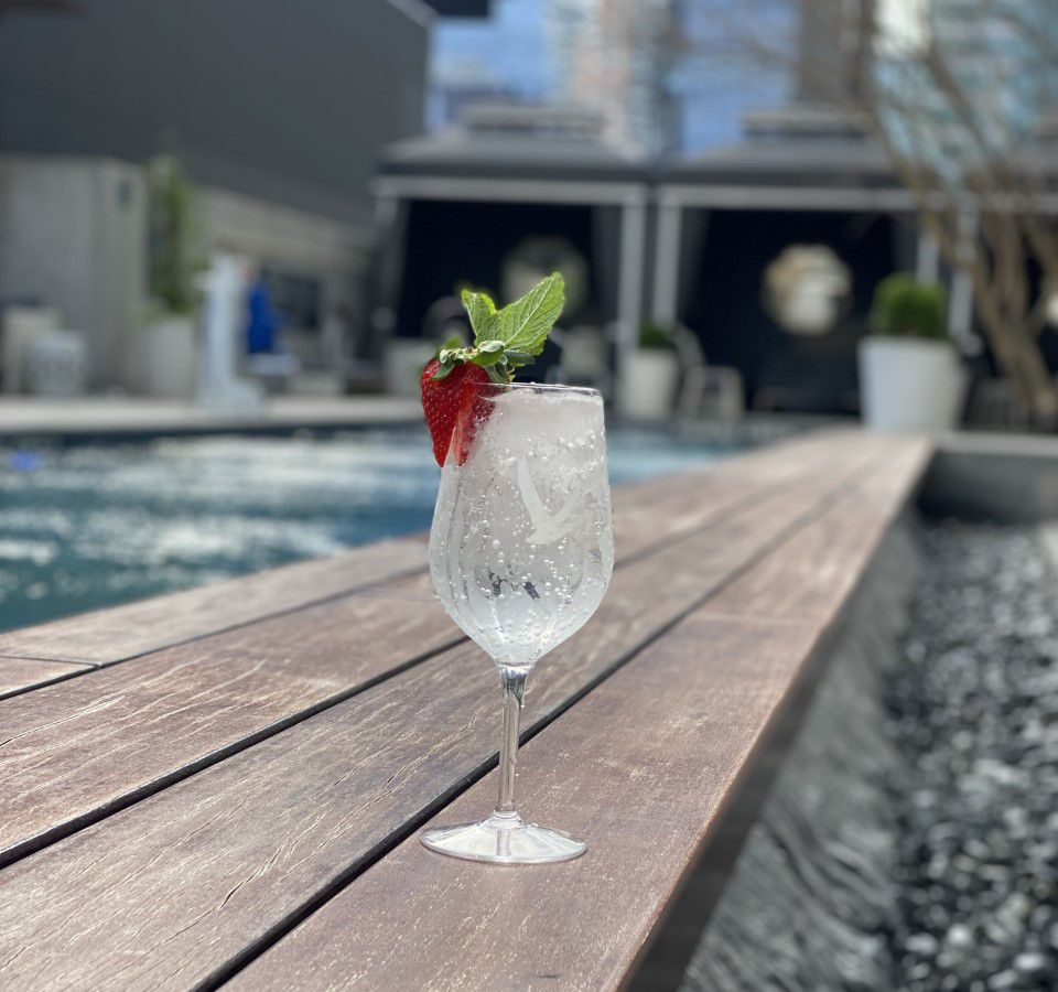 A spritzy, bubbly clear cocktail in a wine glass sitting by a pool is topped with a strawberry slice.