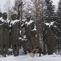 In this Tuesday, April 3, 2012 photo, a man clears snow from the base of a monument at the Samjiyon Grand Monument area in Samjiyon, North Korea at the base of Mount Paektu.