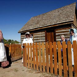 Linda Quitner, left, Dawn Warenski, Zoloma Goodall and Raelou Elsberry stand outside a historic cabin in Santaquin. The four are members of the Daughters of the Utah Pioneers and helped in the restoration of the cabin.