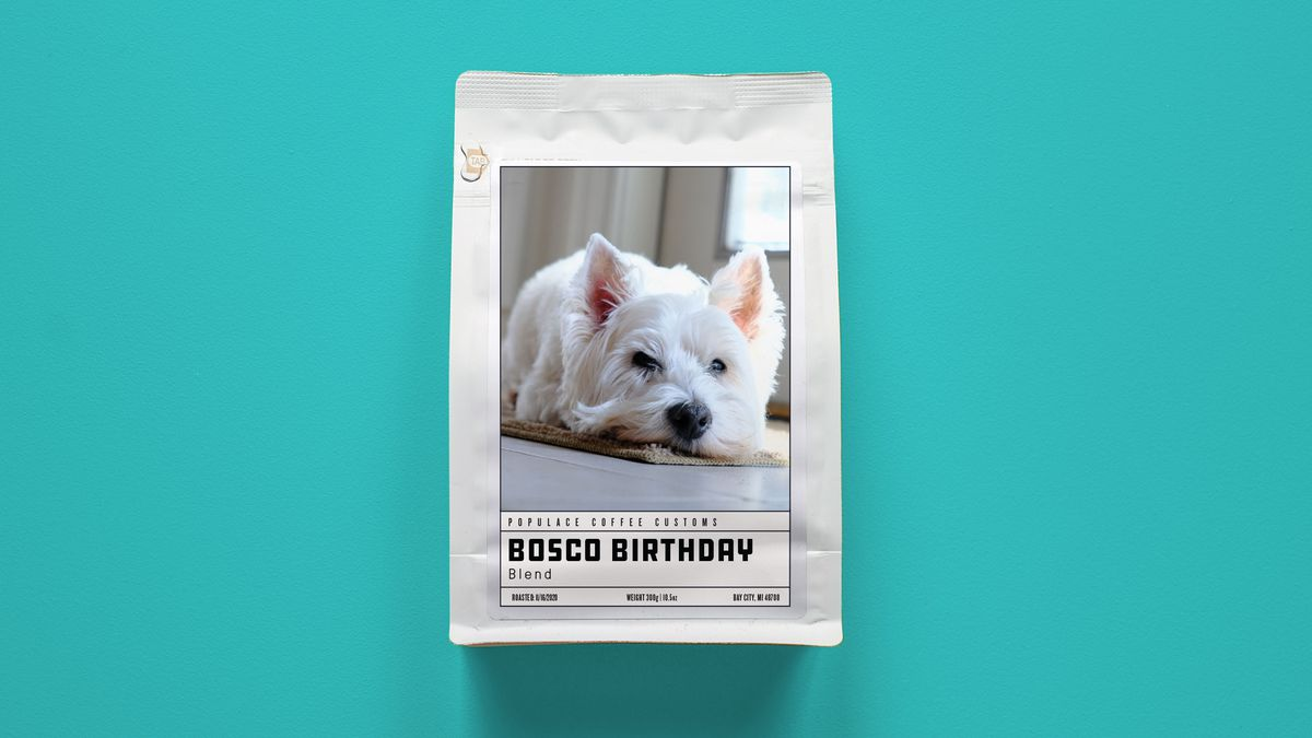"""A white bag of coffee with a photo of a white terrier and the words """"Bosco Birthday"""" blend underneath."""