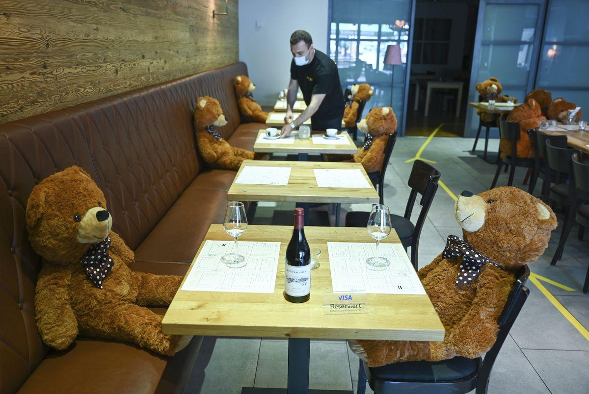 """Manager Musa Gezer prepares tables in his restaurant """"Beef'n Beer"""" besides big teddy bears in Hofheim, Germany, in May."""