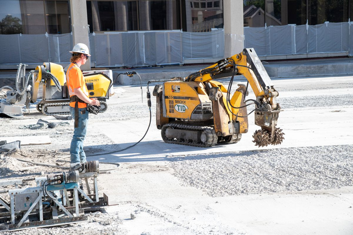 Machines remove damaged concrete in preparation for grout to repair the concrete surface of the Church Office Building plaza.
