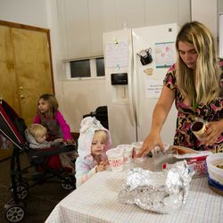 Crissy Norton prepares some packaged foods for dinner as daughters Lucy, 6, left, Julianna, 1, and Adrianna, 3, wait at Lake Washington United Methodist Church in Kirkland, Wash. on Saturday, Oct. 12, 2019. Norton, her husband Matthew Branstetter and three children have been using the Safe Parking program for the past several months.