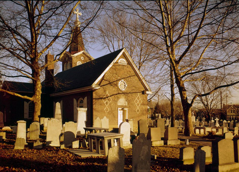 Old Trinity Church in Philadelphia. The facade is brick and there is a graveyard with tombstones and trees in front.