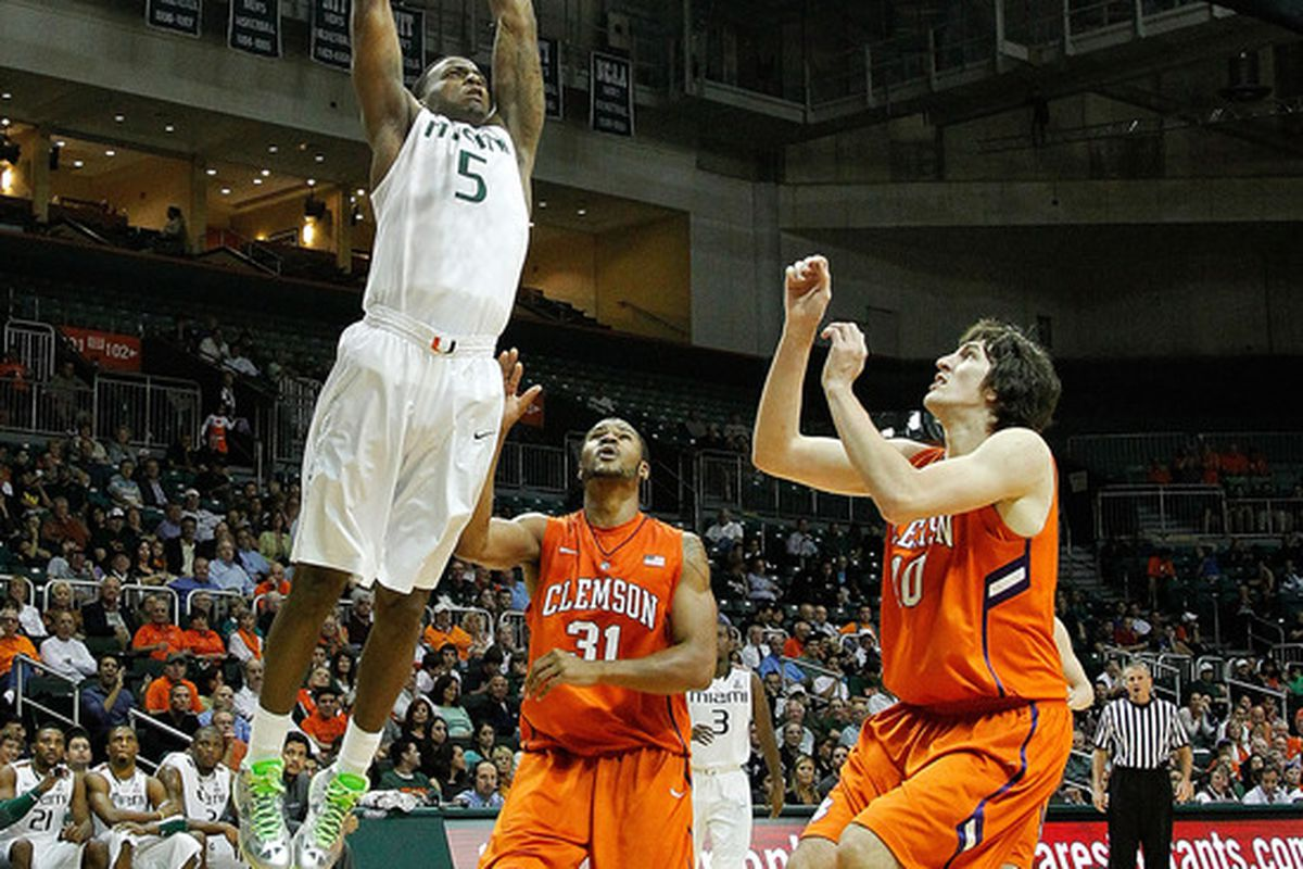 CORAL GABLES, FL - JANUARY 18:  DeQuan Jones #5 of the Miami (Fl) Hurricanes dunks over Devin Booker #31 and Catalin Baciu #10 of the Clemson Tigers during a game  on January 18, 2012 in Coral Gables, Florida.  (Photo by Mike Ehrmann/Getty Images)