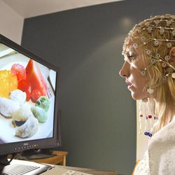 A BYU student wears an EEG recording device to demonstrate how researchers measured neural responses to food after exercise.