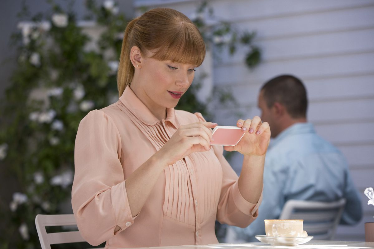 """Bryce Dallas Howard looks at her phone in an image from Black Mirror episode """"Nosedive."""""""