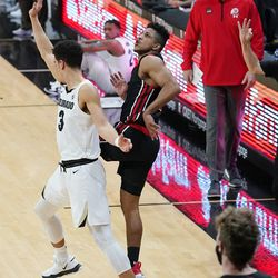 Utah guard Alfonso Plummer, center, follows the flight of his three-point basket over Colorado guard Maddox Daniels (3) to put Utah ahead late in the second half of an NCAA college basketball game Saturday, Jan. 30, 2021, in Boulder, Colo. (AP Photo/David Zalubowski)