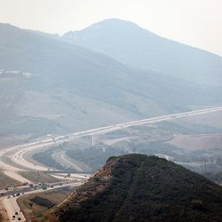Cars travel on SR189 new Jordanelle Reservoir as crews continue fighting the Parleys Canyon Fire near Park City on Sunday, Aug. 15, 2021.