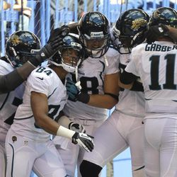 Jacksonville Jaguars wide receiver Cecil Shorts (84) is mobbed by teammates including quarterback Blaine Gabbert (11) after an 80-yard touchdown against the Indianapolis Colts in the final minute of an NFL football game in Indianapolis, Sunday, Sept. 23, 2012. The Jaguars defeated the Colts 22-17.