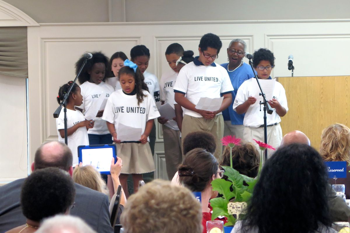 Bridges to Success coordinator Liz Odle and IPS students thank school volunteers and principals at a June celebration honoring the program.