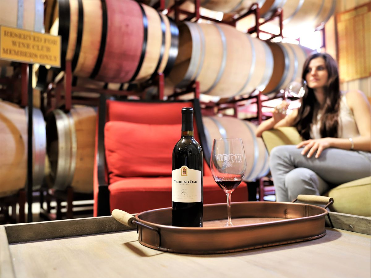 A bottle of Wedding Oak wine and a wine glass filled with a little bit of red sit on a metal tray atop a wooden table; in the background are racks of wine barrels and a woman sitting on a sofa.