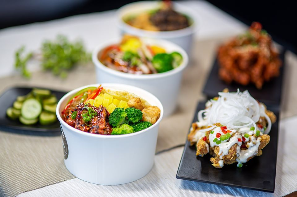 Paper cups containing Korean food beside plates of food