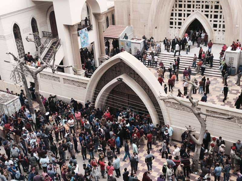 Relatives and onlookers gather outside a church after a bomb attack in the Nile Delta town of Tanta, Egypt, on Sunday.   AP Photo