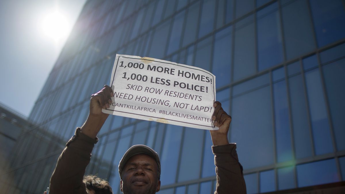 """A protester standing in front of a glass skyscraper is holding a sign that says """"1,000 more homes, 1,000 less police."""""""