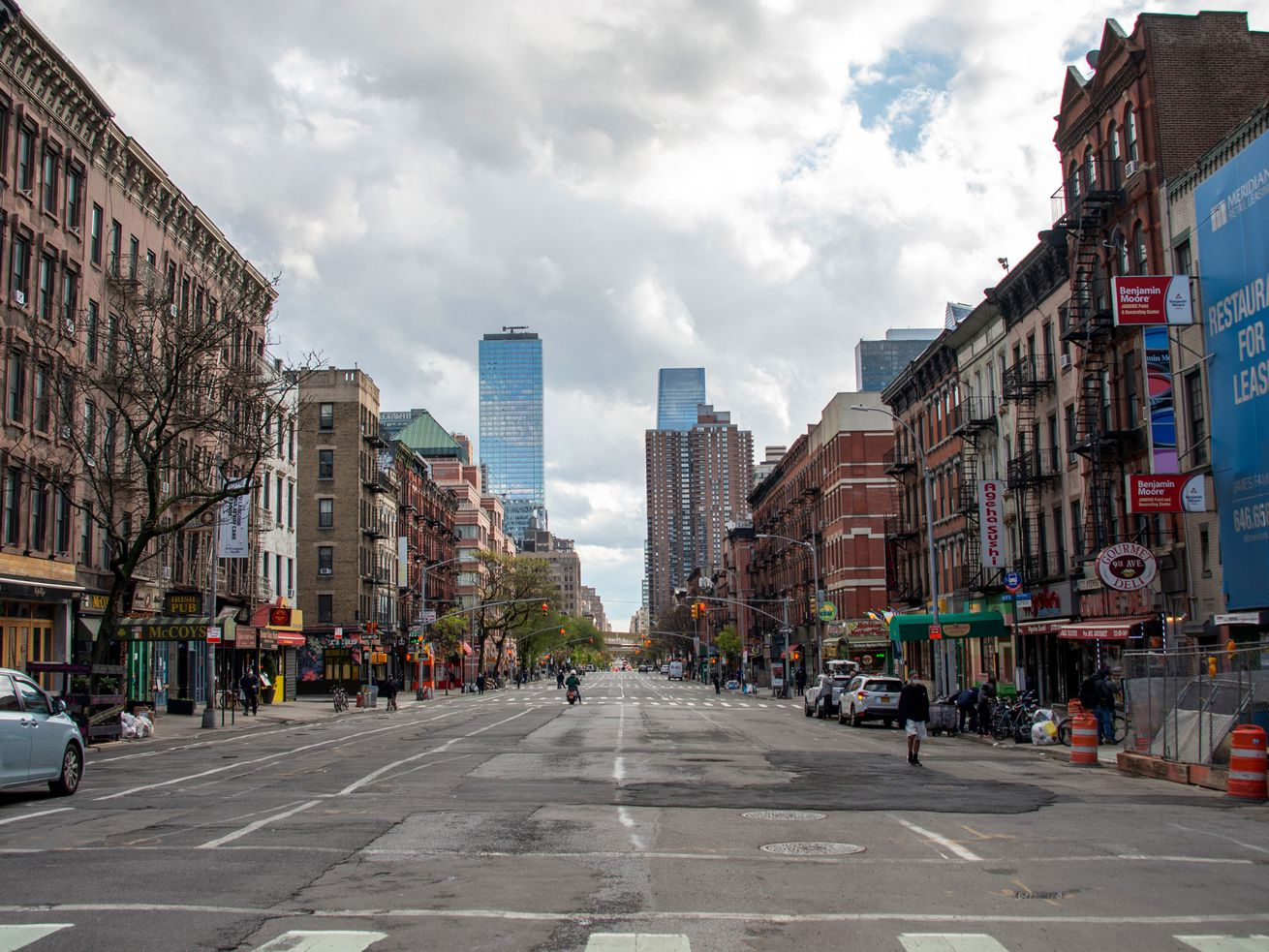 An empty street in New York City shows buildings on either side and a cloudy sky. The image illustrates the state of car buying in New York City during the coronavirus pandemic.