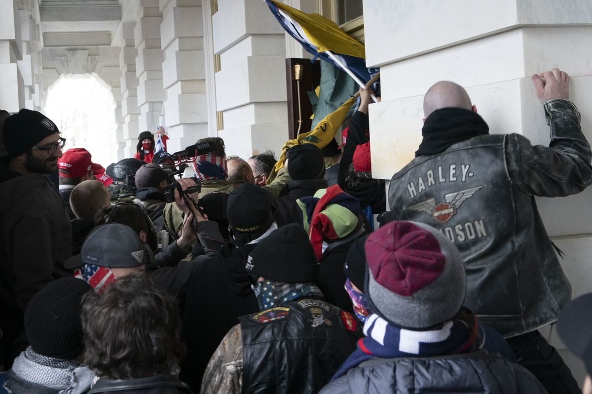 In this Jan. 6, 2021 file photo insurrectionists loyal to President Donald Trump try to open a door of the U.S. Capitol as they riot in Washington.