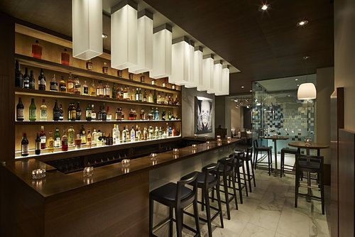 A backlit bar area with black seating and white drop lights
