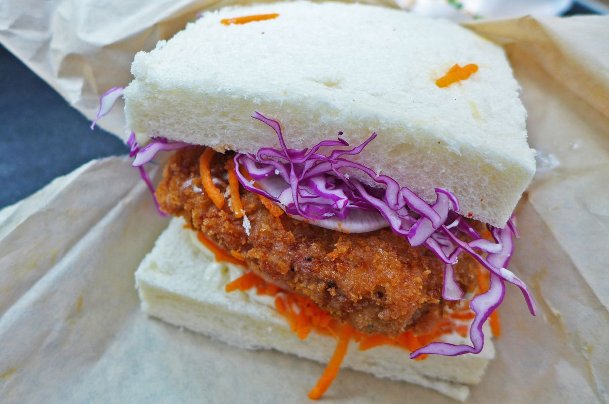 Two square slices of white bread with a crumbed cutlet and orange and purple slaw.