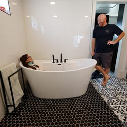 Brooke Andersen, left, talks to her husband, Trevor, as she sits in the tub of their Provo home on Wednesday, July 7, 2021. The couple installed the tub to give her the support she needs. Brooke Andersen's surgery was delayed because of COVID-19 closures, she finally made it to Spain during its brief opening window to have a spinal fusion. Now she can walk again, but she's still facing a lifetime of deterioration from her condition.