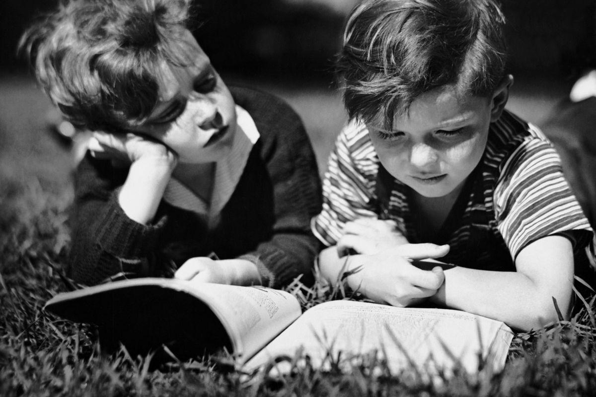 CIRCA 1950s: Two boys reading outdoors.