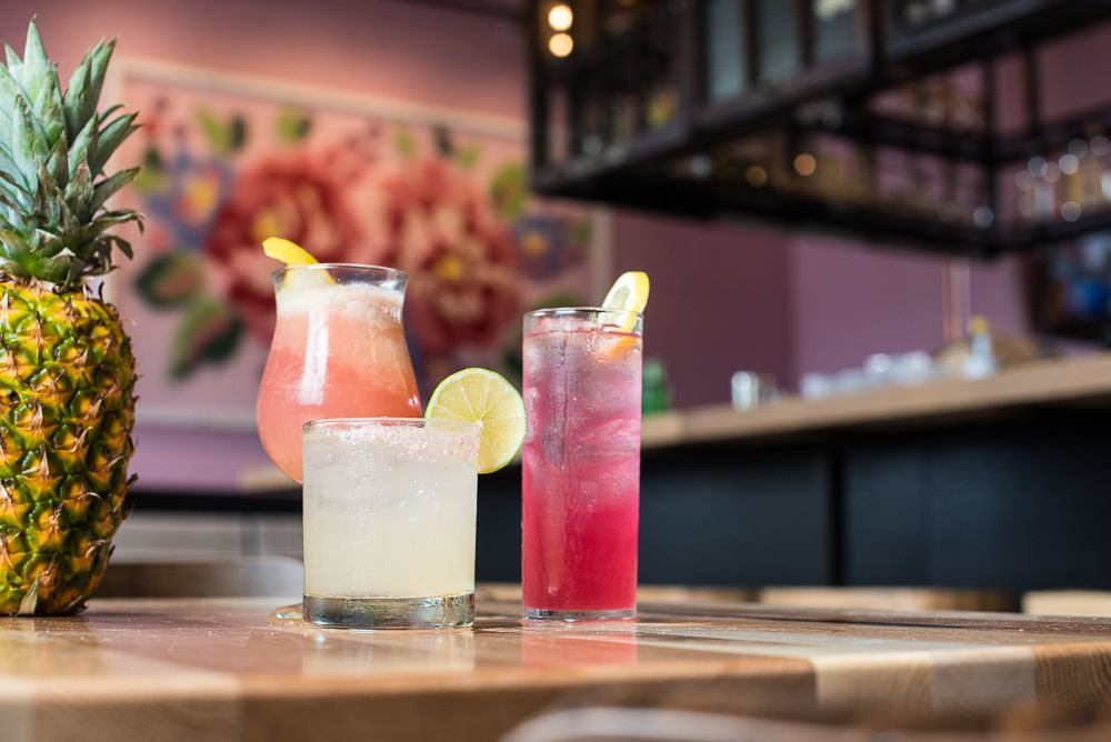 Three brightly colored cocktails in a highball, lowball, and tulip shaped glasses on the wood bar inside Centro. The background shows a bright pink and red cross stitched styled mural.