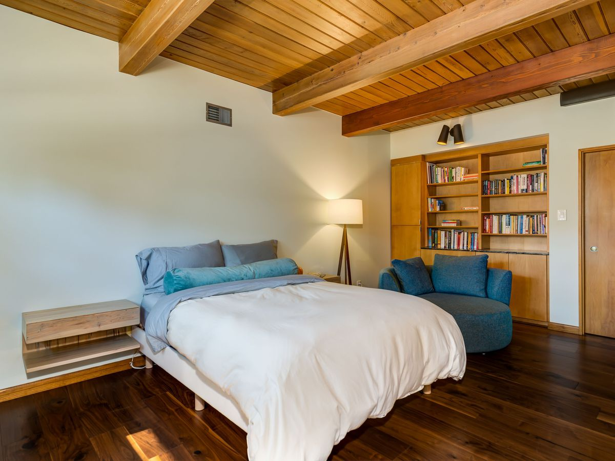 A white bed sits on wooden floors in a room with beamed ceilings.