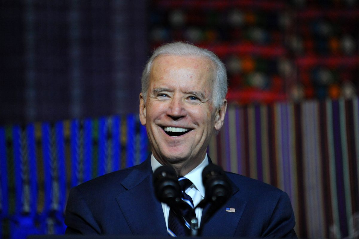 Presidential candidate Joe Biden smiles from behind a microphone.