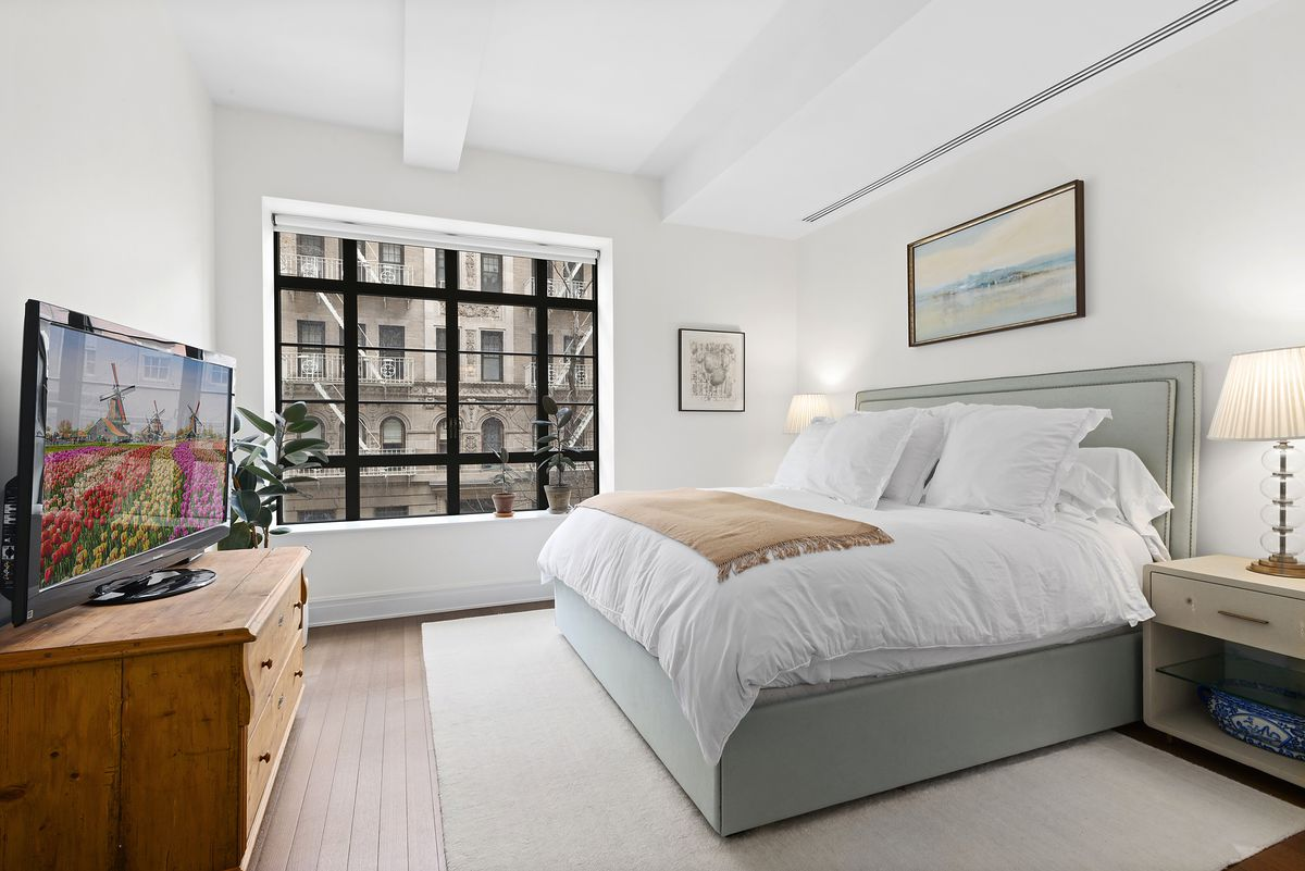 A bedroom with a large bed, a beige rug, a large window, beamed white ceilings, and a TV on a wooden stand.