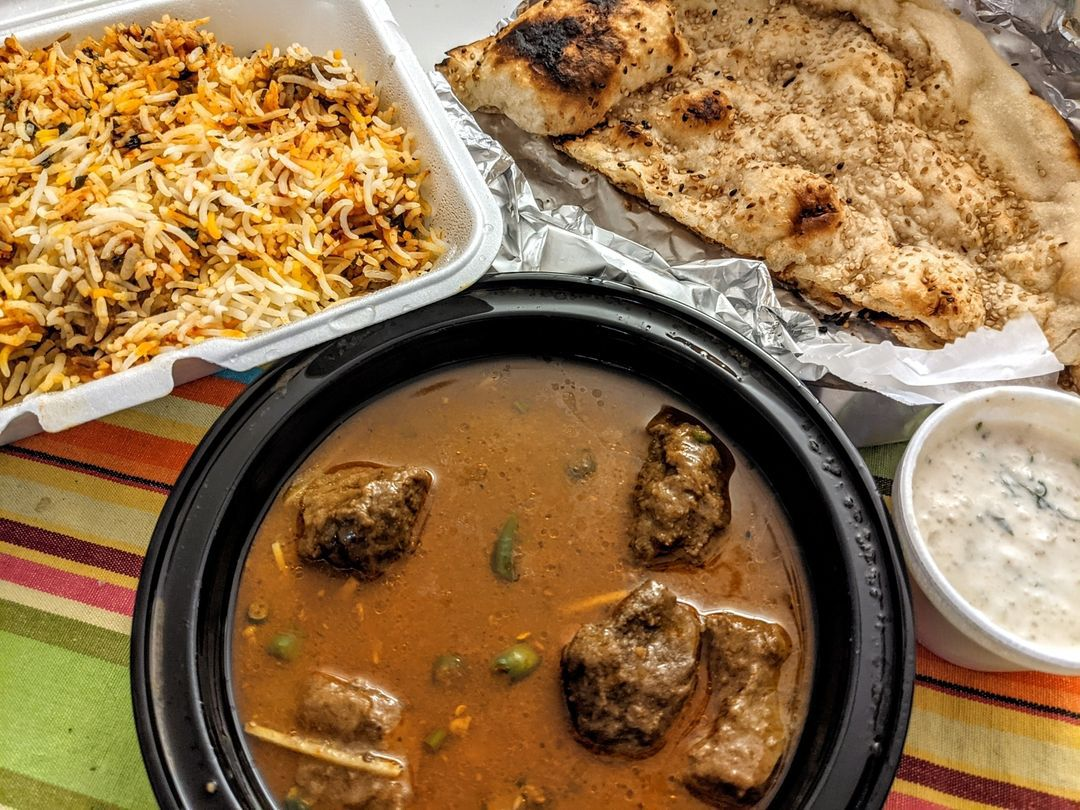 Overhead view of a Pakistani and Indian takeout meal. A white styrofoam container is filled with rice and hunks of lamb, a black plastic bowl has a thin, brown stew with chunks of beef, and there's a large sesame-topped piece of naan on a piece of aluminum foil. There's also a small white styrofoam bowl of a yogurt sauce. A multi-colored striped tablecloth is visible underneath it all.
