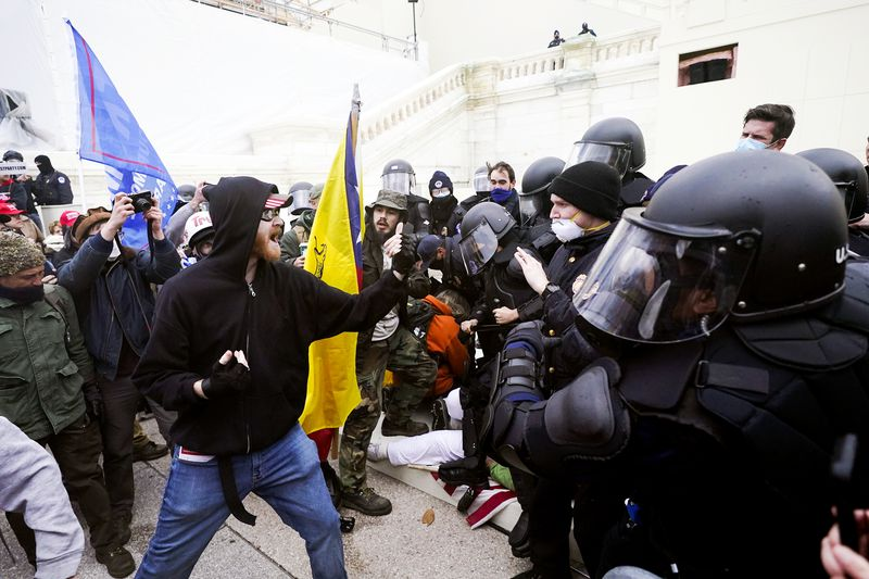 A dense crowd stands behind a white man in a black hoodie and blue jeans who waves his fist and shouts at police clad in riot gear, their helmet visors down. A blue and red Trump-Pence flags waves behind the man in black.