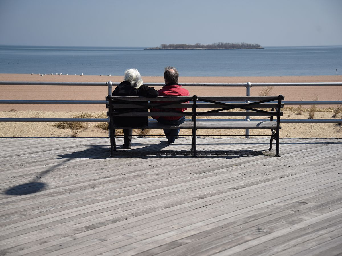 A beach boardwalk. There is a bench with a man and a woman sitting on it. They are looking out at a sandy beach and the ocean.
