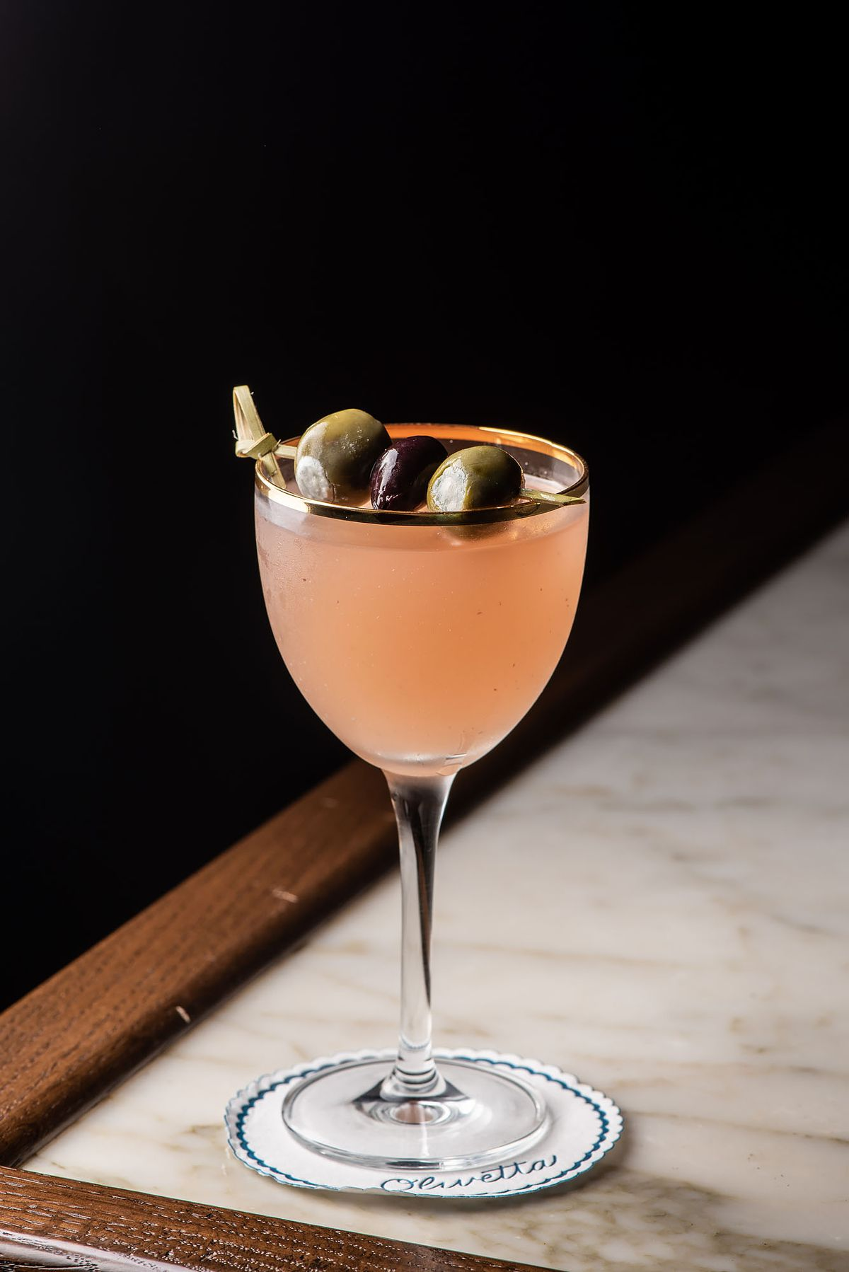 A tall peach cocktail with two olives.