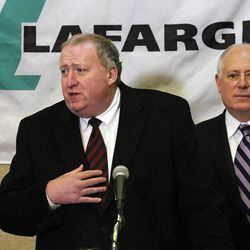 John Stull, CEO of Lafarge, speaks at a news conference Tuesday, April 17, 2012, in Rosemont, Ill., with Illinois Gov. Pat Quinn listening, after is was announced that concrete manufacturing company Lafarge North America is moving its North America headquarters to Illinois from Virginia and will create up to 100 jobs. Stull says the factors in their decision were location in the Midwest and area transportation. Lafarge is a subsidiary of Lafarge SA, which is based in France.