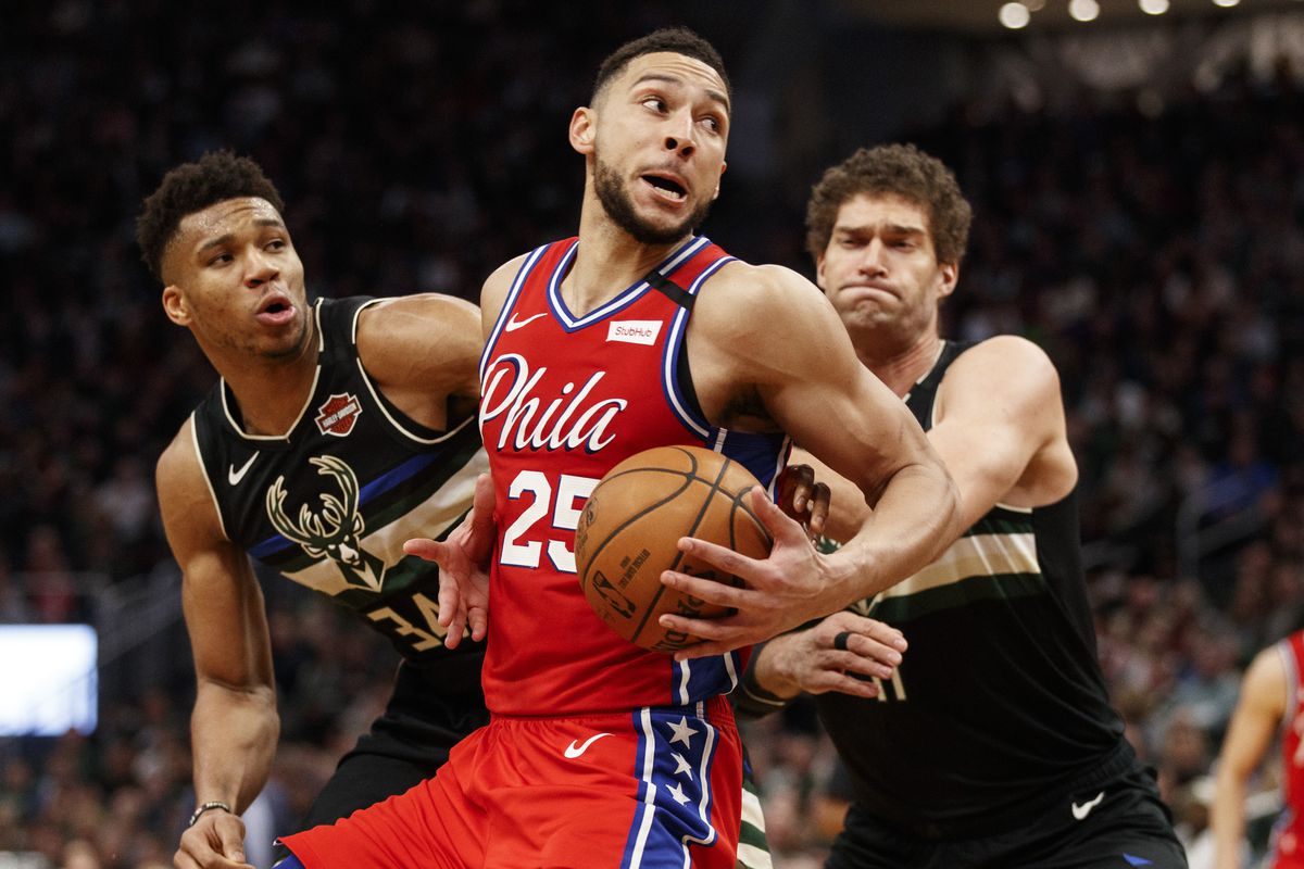 Philadelphia 76ers guard Ben Simmons spins to the basket against Milwaukee Bucks forward Giannis Antetokounmpo and center Brook Lopez during the fourth quarter at Fiserv Forum.