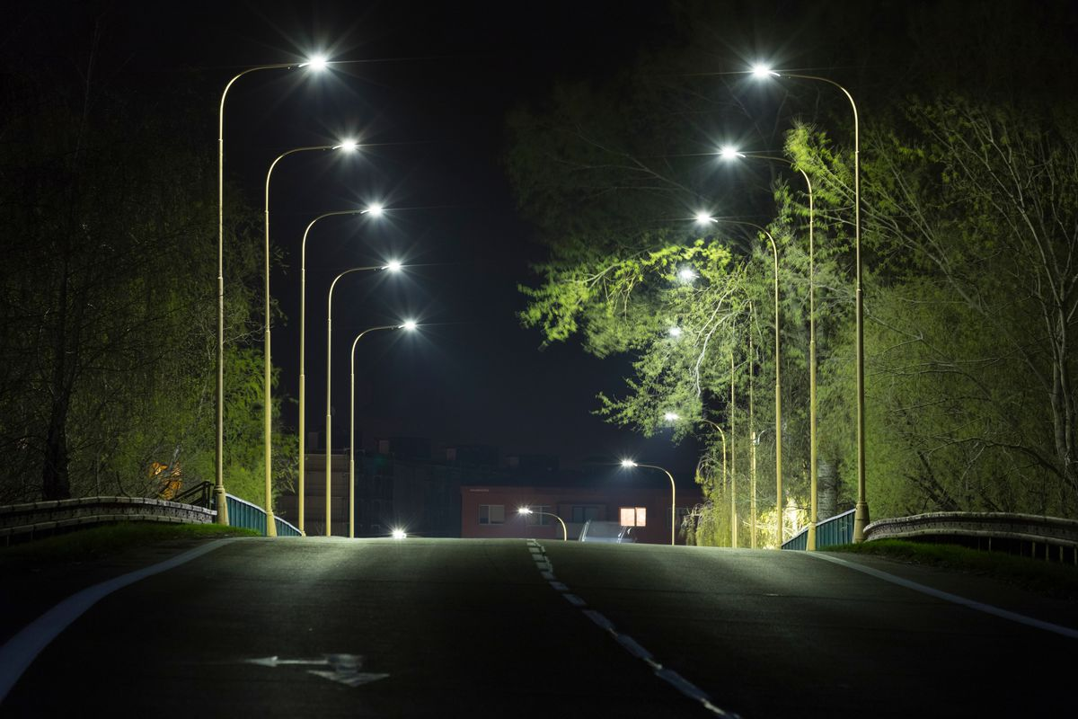 Two rows of LED streetlights on either side of a road at night.