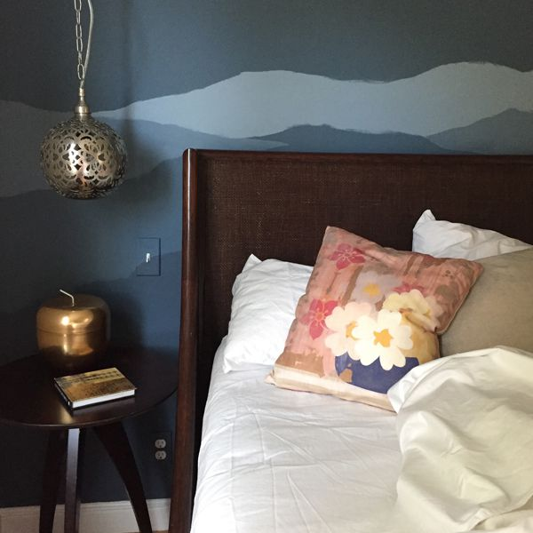 An accent wall in a bedroom is painted a deep shade of blue, with a mural on top.