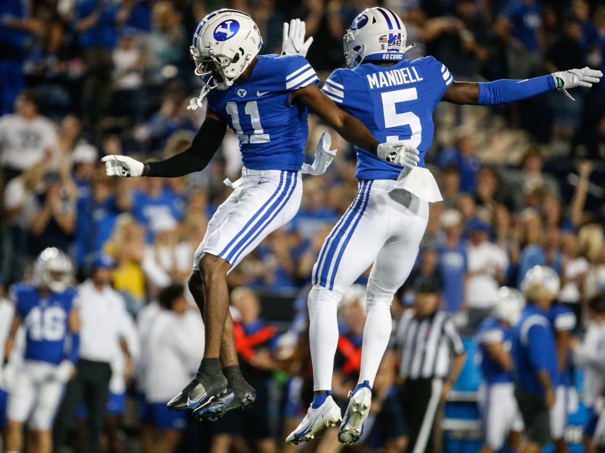 Brigham Young Cougars D'Angelo Mandell and Isaiah Herron celebrate an interception during the first half of game in Provo.