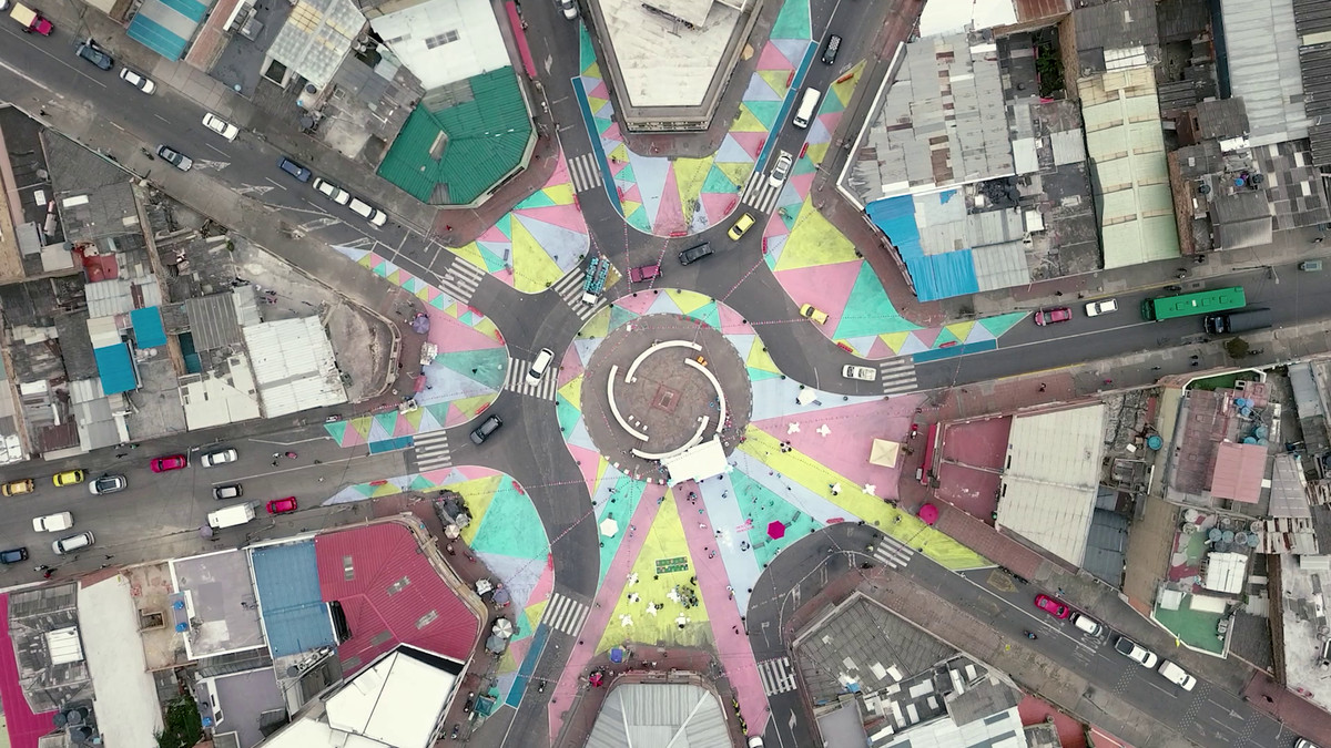 An aerial shot shows eight streets coming together in a traffic circle that's been painted in colorful stripes to narrow the lanes for cars.