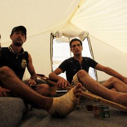 Ayman Jamoos, 24, left, and Hamza jamoos, 23, former Free Syrian Army fighters, pose inside their tent, at Zaatari Refugee Camp, in Mafraq, Jordan, Sunday, Sept. 2, 2012. The Jamoos brothers were injured in Daraa just a few days ago from shelling.