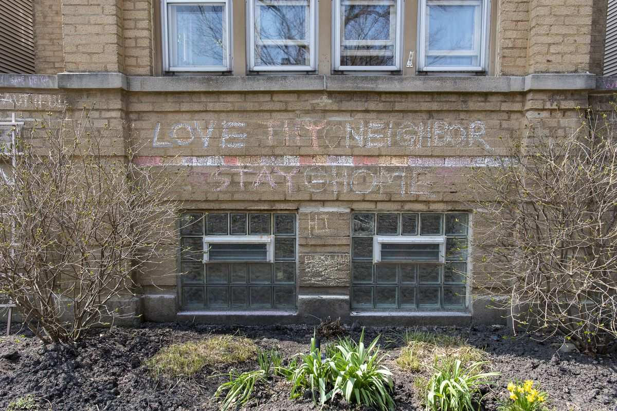 "A building with a chalk sign that asks to ""Love Thy Neighbor"" and to ""Stay Home"" in the Albany Park neighborhood, Tuesday."