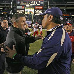 Utah coach Kyle Whittingham and Navy coach Ken Niumatalolo talk after the Poinsettia Bowl in San Diego on Dec. 20, 2007.