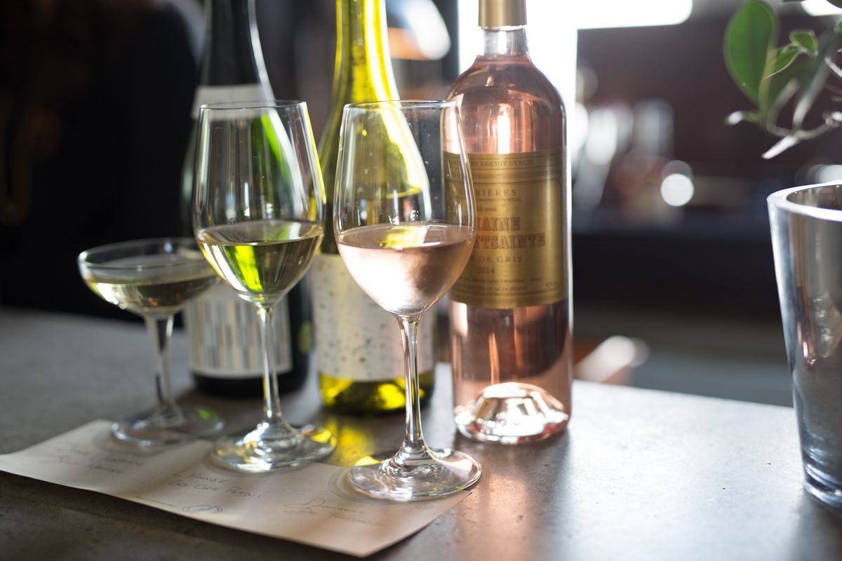 A table at Bottlehouse shows two wine glasses (one white, one rose) and bottles behind them.