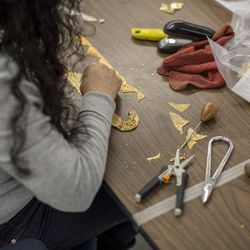 A worker cuts pieces from the chain mesh to prepare for jewelry.