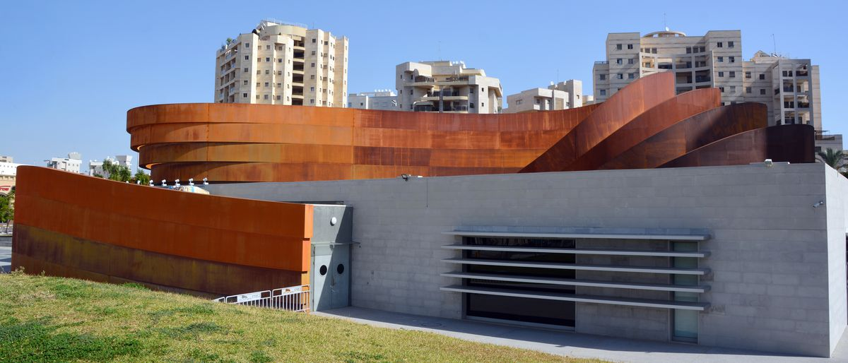 The exterior of the Design Museum Holon in Israel. The facade is grey and with rust colored steel bands on the roof.  In the distance is a row of city buildings.