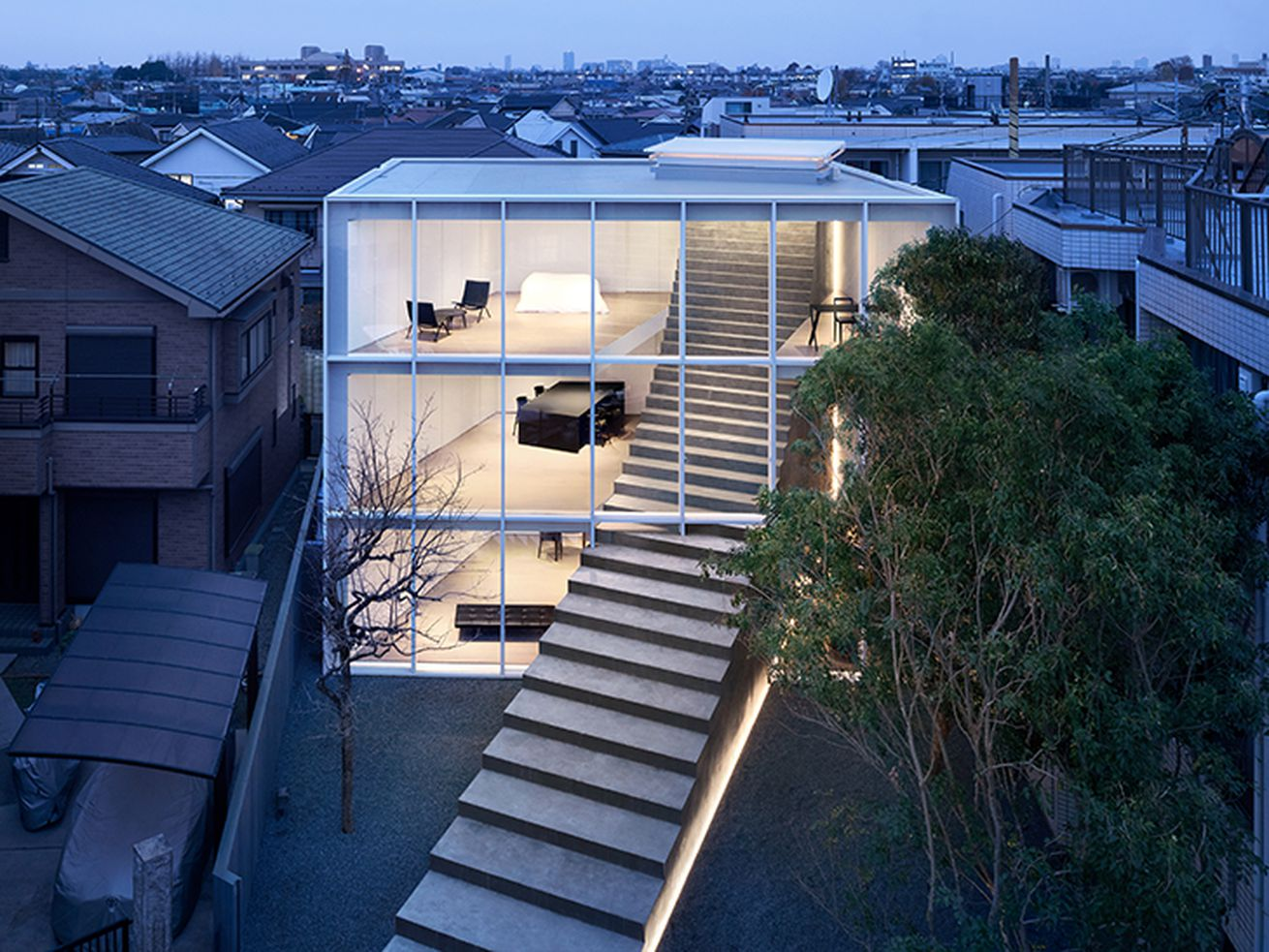 Exterior shot of house lit up at night with a huge staircase running through a glass facade.