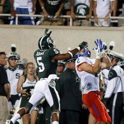Boise State's Matt Miller (2) catches a pass for a 40-yard reception against Michigan State's Johnny Adams (5) during the second quarter of an NCAA college football game, Friday, Aug. 31, 2012, in East Lansing, Mich.