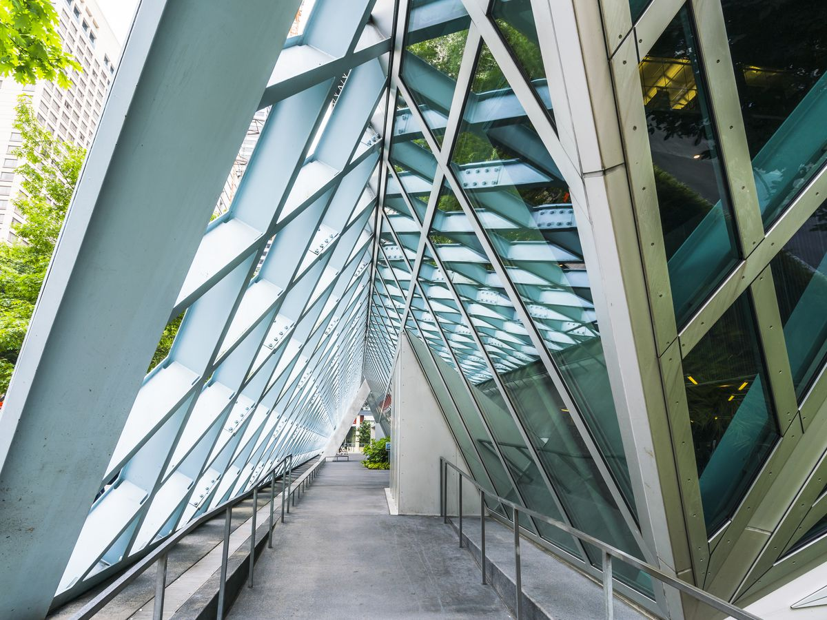 An outdoor pathway along a building covered in glass, latticed windows.An angular, open, latticed wall covers the walkway to make a triangle.