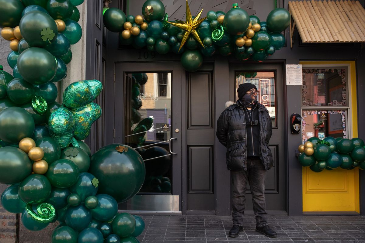 A guard stands outside Miki's Park in River North on Saturday. Bars will again be operating at 50% capacity on St. Patrick's Day.